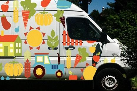 Photo : camionnette blanche couverte de petits dessins de légumes, maisons, arrosoirs, etc.